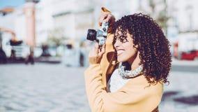 有减速火箭的照片照相机的卷曲美丽的妇女 免版税库存图片