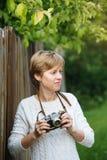 有减速火箭的照片照相机的女孩在户外篱芭附近 免版税库存图片