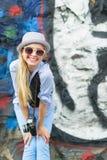 有减速火箭的照片照相机的微笑的女孩对都市墙壁户外 免版税库存图片