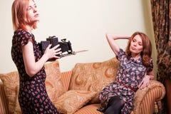 有减速火箭的照相机的二名妇女 免版税库存照片