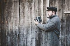 有减速火箭的照相机的在手上,表面无光泽的作用古板的摄影师 想法-戏院产业,电影第70 库存照片