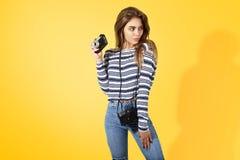 有减速火箭的照相机的性感的女孩在黄色背景 免版税库存照片