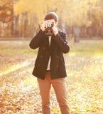 有减速火箭的葡萄酒照相机的英俊的人在秋天 库存照片