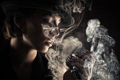 有减速火箭的话筒的歌手妇女在烟 免版税库存图片