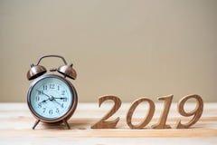 有减速火箭的闹钟的2019新年快乐和在桌和拷贝空间的木数字 新的开始、决议、目标和使命 免版税库存照片