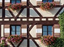 有几朵窗口快门和花的半木料半灰泥的房子 免版税库存照片