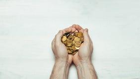 有几枚硬币的男性手在轻的白色背景的棕榈 平的样式 免版税图库摄影