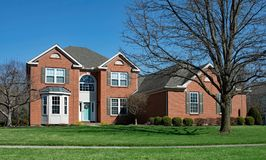 有凸出的三面窗&被成拱形的词条的大红砖家 库存照片