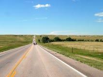 有凹凸地形的南达科他开放路,在车行道的车 免版税库存照片