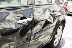 有凹痕的黑汽车 免版税库存图片