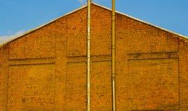 有出气孔的红砖墙壁用管道输送,纹理背景 免版税库存图片
