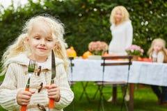 有刀子和叉子的白肤金发的女孩 免版税库存照片