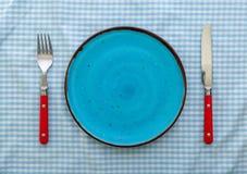 有刀子和叉子的空的蓝色陶瓷板材 库存照片