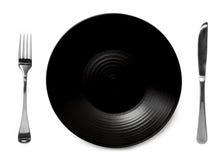 有刀子和叉子的黑色的盘子 免版税图库摄影