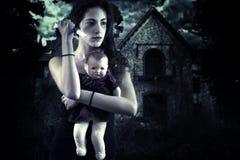 有刀子和玩偶的十几岁的女孩在一个被困扰的房子前面 库存照片
