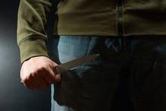有刀子武器的一名罪犯威胁杀害 罪行,罪行,盗案恶棍 免版税库存照片