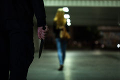 有刀子的人在妇女之后 库存图片