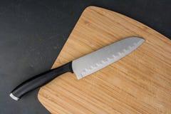 有刀子的切板在黑柜台渔了 图库摄影