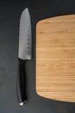 有刀子的切板在黑柜台 图库摄影
