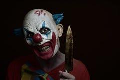 有刀子的可怕邪恶的小丑 免版税库存图片