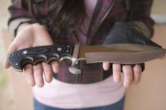 有刀子的女性强盗在她的棕榈 库存照片