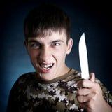 有刀子的恼怒的少年 免版税库存图片