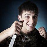 有刀子的恼怒的少年 免版税库存照片