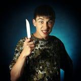 有刀子的恼怒的少年 库存图片