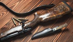 有刀子的狩猎设备在老木背景 库存照片
