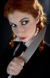 有刀子的疯狂的女小学生 库存图片