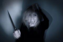 有刀子的精神病妇女 库存图片