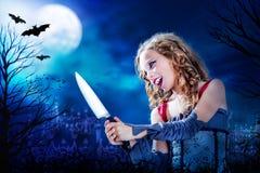 有刀子的年轻吸血鬼在满月 免版税图库摄影