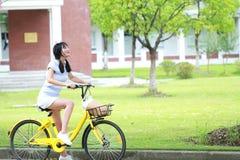 有分享的自行车亚裔中国年轻美丽,优美加工好的妇女 秀丽、时尚和生活方式 免版税库存图片