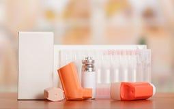 有分配器和一箱的两个便携式吸入器在桌上的细颈瓶 图库摄影