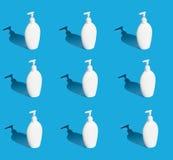 有分配器的很多白色瓶在蓝色背景 免版税库存图片