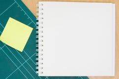 有切口席子的笔记本在木桌上,空白的笔记本,岗位 库存图片