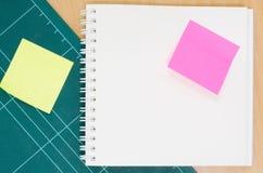 有切口席子的笔记本在木桌上,空白的笔记本,岗位 库存照片