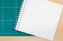 有切口席子的笔记本在木桌上,空白的笔记本,岗位 免版税库存图片