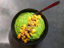 有切好的芒果和chia种子的绿色圆滑的人碗 免版税库存照片