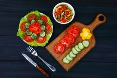 有切片的一个切板蕃茄、黄瓜和胡椒、叉子和刀子和菜沙拉,健康食品两块板材  免版税库存照片
