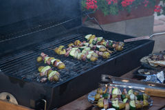有切片的串土豆,夏南瓜,烟肉,蘑菇,葱,撇蓝烤了在烤肉格栅的木炭 免版税图库摄影