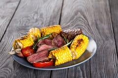 有切片的蓝色黏土板材温和地油煎的牛排和玉米 免版税库存图片