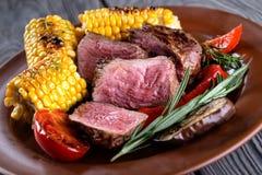 有切片的黏土板材切好的捐赠的肉和玉米 免版税库存照片