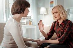 有刚毅白肤金发的妇女重要严肃的交谈 免版税图库摄影
