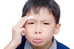 有创伤的男孩在膏药的顶头盖子 库存照片