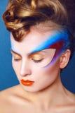 有创造性的妇女在蓝色背景组成和发型 免版税库存图片