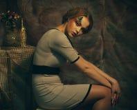 有创造性的时装模特儿妇女做坐在戏曲装饰的一把凳子 免版税库存照片