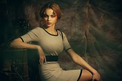 有创造性的时装模特儿妇女做坐在戏曲装饰的一把凳子 库存照片