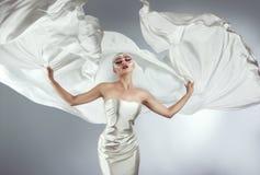 有创造性的构成的妇女在一次白色布料飞行 拿着飞行白色布料的女孩 免版税库存图片