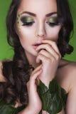 有创造性的深色的树精妇女在她的面孔、卷发和服装组成和小珠由叶子制成在绿色backgro 免版税库存图片